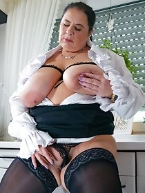 Big breasted mature posing solo in dark lingerie